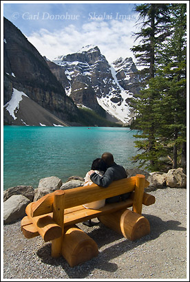 Tourists enjoy the view lakeside, at Moraine Lake, Banff National Park, Alberta, the Canadian Rockies, Canada.