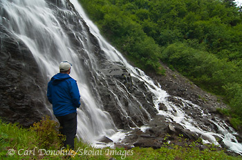 A hiker stands alongside Horsetail Falls, near Valdez, on the Richardson Highway, Alaska.